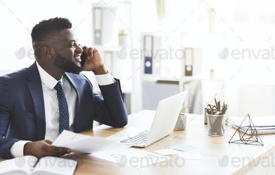 Smiling black businessman checking reports, talking by phone with assistant