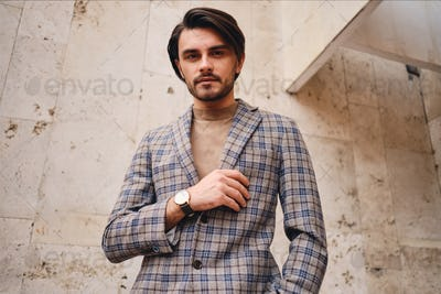 Young handsome man in stylish checkered jacket confidently looking in camera outdoor