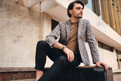 Young attractive man in stylish checkered jacket confidently looking away outdoor