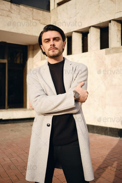 Young handsome serious stylish man in coat with crossed hands confidently looking in camera outdoor