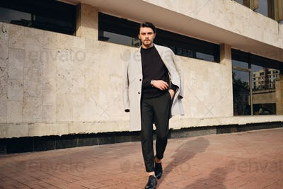 Young handsome stylish man in coat confidently looking in camera walking outdoor