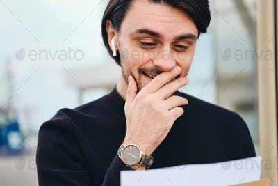 Young smiling brunette man joyfully reading envelope with response outdoor