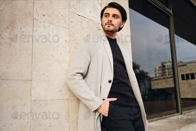 Young confident stylish man in coat with hand in pocket thoughtfully looking away outdoor