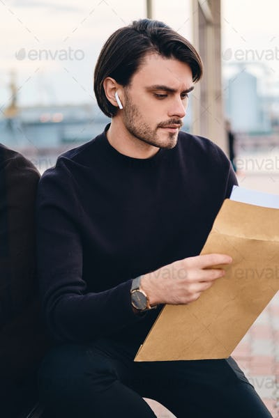 Young handsome confident man thoughtfully reading envelope with response from job outdoor