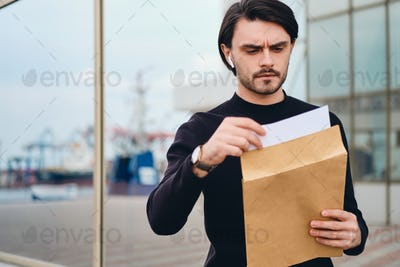 Young serious brunette man angrily opening envelope with response outdoor