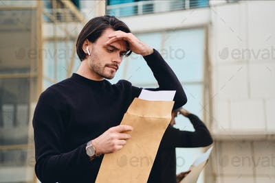 Young sad brunette man thoughtfully reading envelope with response outdoor