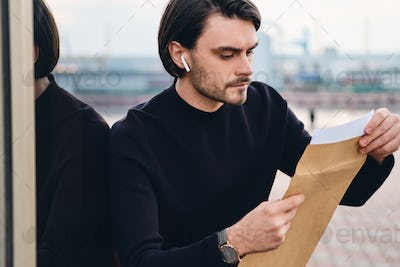 Young handsome serious man confidently opening envelope with response outdoor