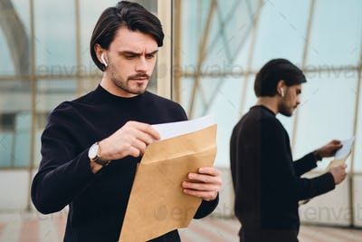 Portrait of young serious brunette man angrily reading envelope with response outdoor