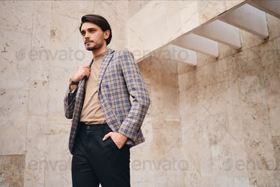 Young attractive stylish man in checkered jacket thoughtfully looking away outdoor