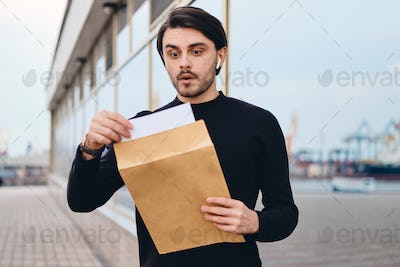 Young excited brunette man amazedly opening envelope with response outdoor