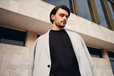 Young attractive stylish brunette man in coat slyly looking in camera outdoor