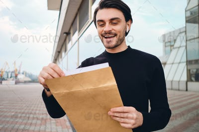 Young cheerful brunette man happily opening envelope with response from job outdoor
