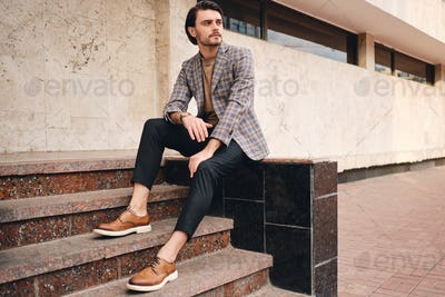 Young handsome stylish man in checkered jacket thoughtfully looking away sitting outdoor