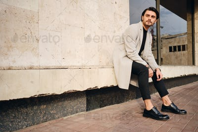 Young handsome casual man in coat thoughtfully looking away sitting on street