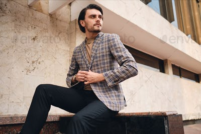 Young handsome confident man in stylish checkered jacket intently looking away outdoor