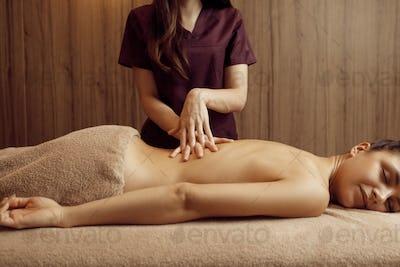 Female masseur pampering back to woman, massage