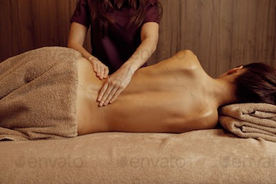 Female masseur pampering ribs to young slim woman