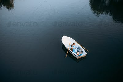 Love couple lying in a boat on lake, top view