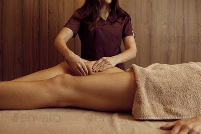 Masseur pampering legs to woman, closeup view