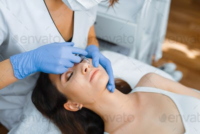 Cosmetician gives face botox injections to patient