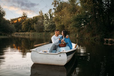 Love couple hugs in a boat on quiet lake at sunset