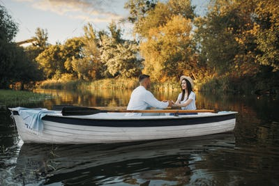 Love couple boating on lake, romantic meeting