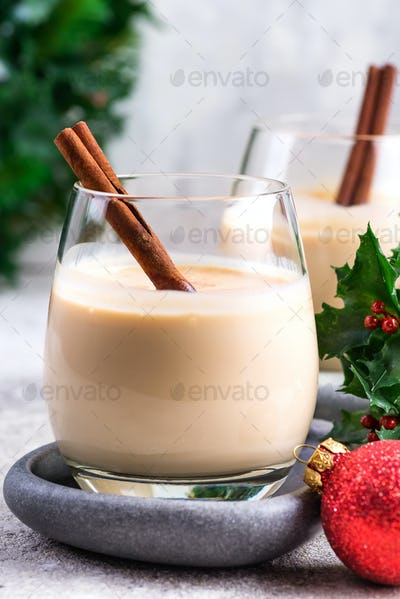 New Year or Christmas Eggnog cocktail with cinnamon and nutmeg in a glass, branches of holly berries