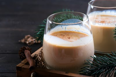 Eggnog Christmas milk cocktail with cinnamon, served in two glasses on vintage tray with fir branch