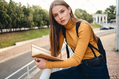 Attractive student girl with text book thoughtfully looking in camera studying in city park