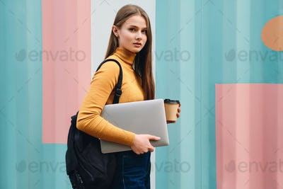 Student girl with laptop and coffee to go thoughtfully looking in camera over colorful background