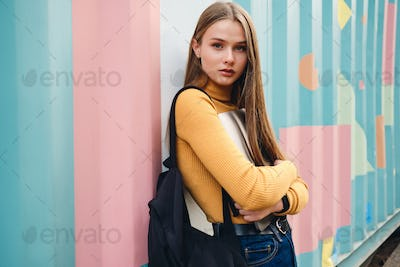 Pretty casual student girl with laptop intently looking in camera over colorful background