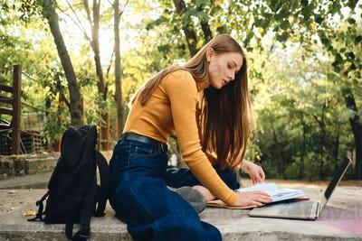 Side view of attractive student girl studying with laptop and book in city park