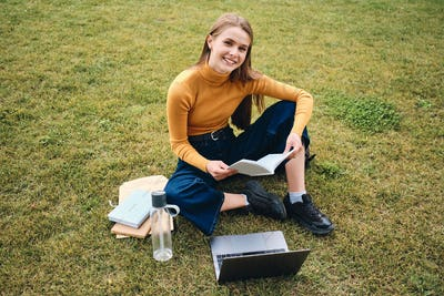 Attractive cheerful student girl happily looking in camera studying on lawn in park