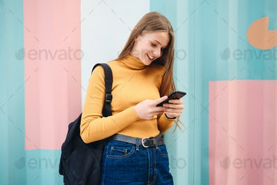 Attractive smiling student girl joyfully using cellphone over colorful background outdoor