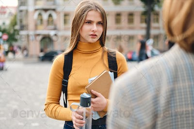 Serious casual student girl sadly talking with friend during study break outdoor