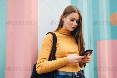 Attractive casual student girl using cellphone over colorful background outdoor