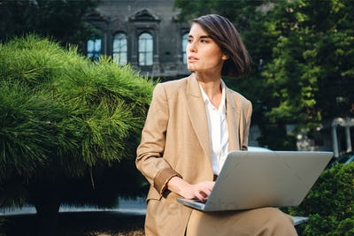 Young beautiful stylish businesswoman in suit dreamily working on laptop outdoor