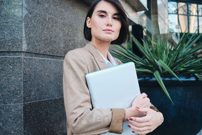Young attractive stylish businesswoman with laptop intently looking in camera on street