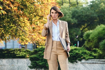 Young confident stylish businesswoman talking on cellphone intently looking in camera on street