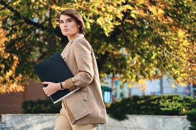 Young beautiful stylish businesswoman with folder thoughtfully walking on street