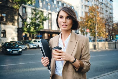Young beautiful businesswoman with laptop and coffee to go on city street
