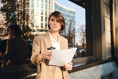 Young beautiful serious businesswoman with coffee to go thoughtfully working on street