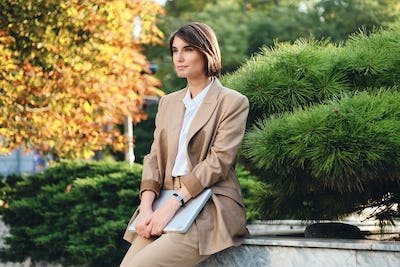 Young attractive stylish businesswoman in suit with laptop dreamily looking away outdoor