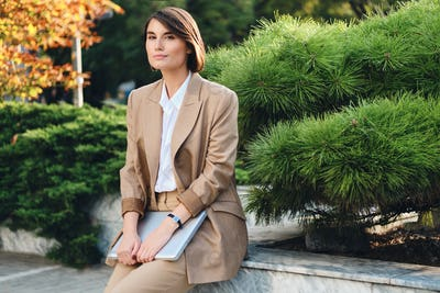 Young beautiful stylish businesswoman in suit with laptop dreamily looking in camera resting outdoor