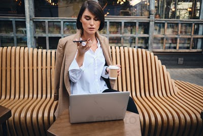Confident stylish businesswoman with laptop recording voice message on cellphone during coffee break