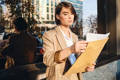 Young attractive stylish businesswoman confidently working with papers on street