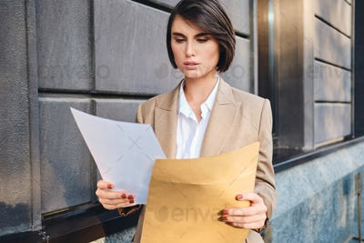 Young serious businesswoman in suit thoughtfully working with papers on street