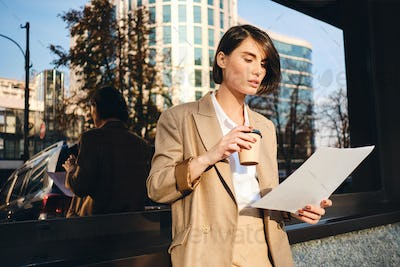 Young confident stylish businesswoman with coffee to go working on street