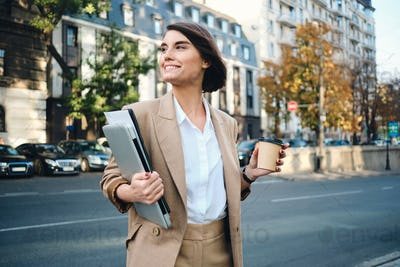 Young beautiful happy businesswoman with laptop and coffee to go on city street