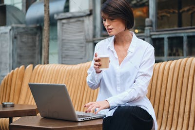 Young attractive businesswoman working on laptop during coffee break in cafe on street